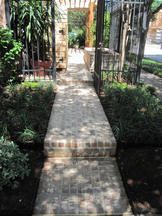 Brick path in shady front garden.
