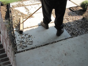 Installing rainbow gravel between cement pads.