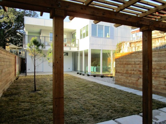 Pergola, lawn and pine trees.